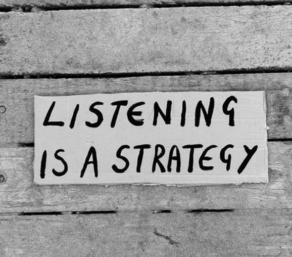 A sign that says Listening is a Strategy