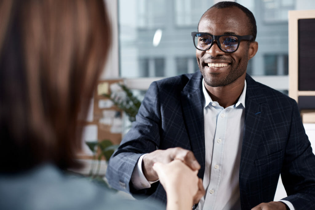 Man shaking a woman's hand at a job interview