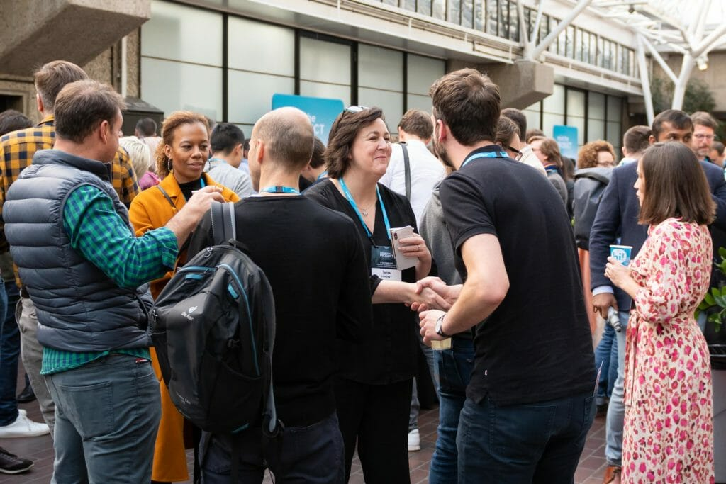 People chatting at a product management networking event